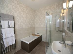 En suite with bath tub and shower